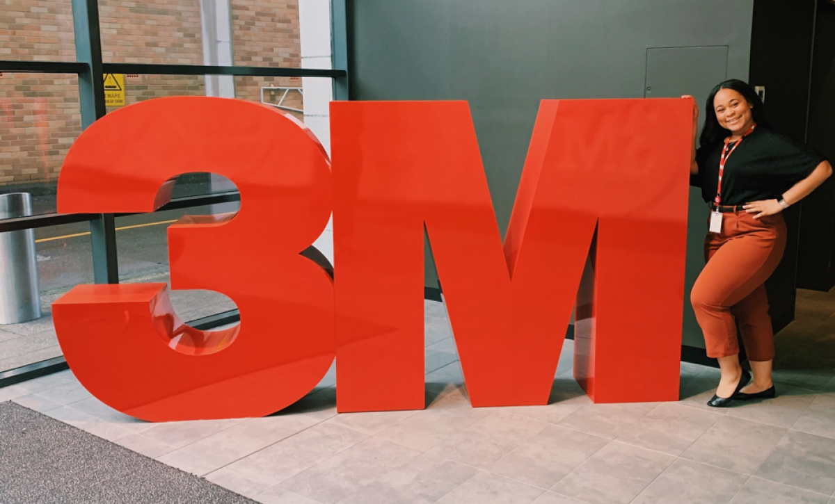 woman standing next to large 3M logo in office space